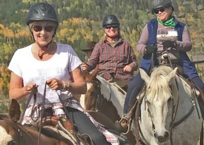 Women at the retreat riding horses on a trail ride.